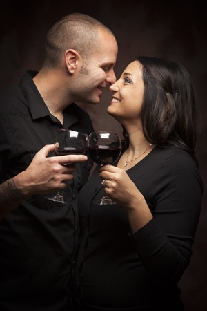 Happy Mixed Race Couple Flirting and Holding Wine Glasses on a Dark Background.