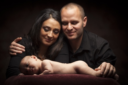 Mixed Race Couple Lovingly Look On While Baby Lays on Pillow on a Dark Background. Stock Photo - 13246165