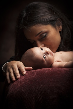 Young Attractive Ethnic Woman Holding Her Newborn Baby Under Dramatic Lighting