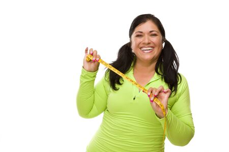 Attractive Middle Aged Hispanic Woman In Workout Clothes Showing off Her Tape Measure Against a White Background. photo
