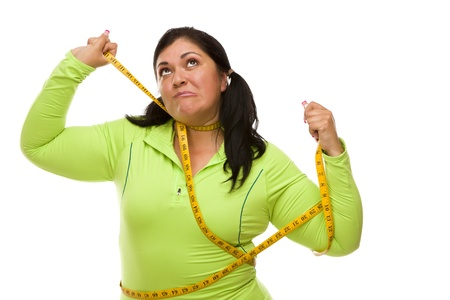 aggravated: Attractive Frustrated Hispanic Woman Tied Up With Tape Measure Against a White Background. Stock Photo