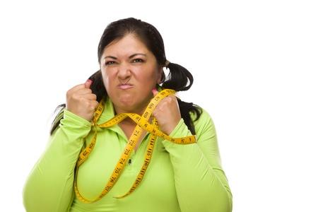 Attraktive Frustriert Hispanic Frau Tied Up mit Maßband vor einem weißen Hintergrund.