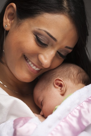 ethnic mix: Young Attractive Ethnic Woman Holding Her Newborn Baby Under Dramatic Lighting.