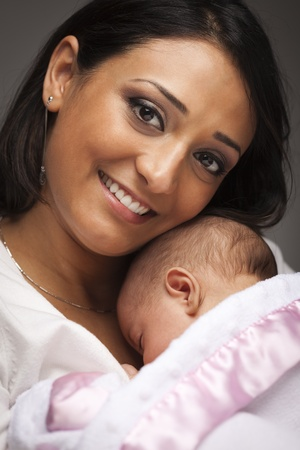 newborn baby mother: Young Attractive Ethnic Woman Holding Her Newborn Baby Under Dramatic Lighting.