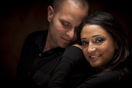 minority couple: Happy Mixed Race Couple Flirting with Each Other Portrait Against A Black Background. Stock Photo
