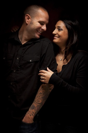 mixed race person: Happy Mixed Race Couple Flirting with Each Other Portrait Against A Black Background. Stock Photo