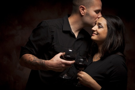Happy Mixed Race Couple Flirting and Holding Wine Glasses on a Dark Background. photo