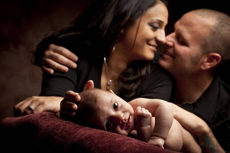 Mixed Race Couple Lovingly Look On While Baby Lays on Pillow on a Dark Background.