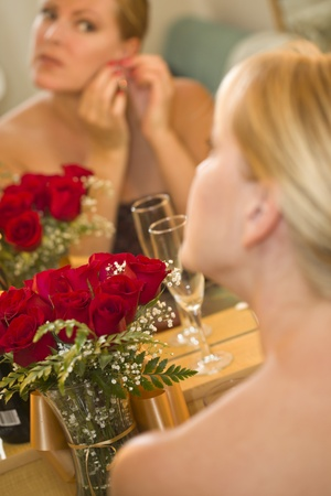 Attractive Blonde Woman Applies Her Makeup at a Mirror Near Champagne and Roses. photo