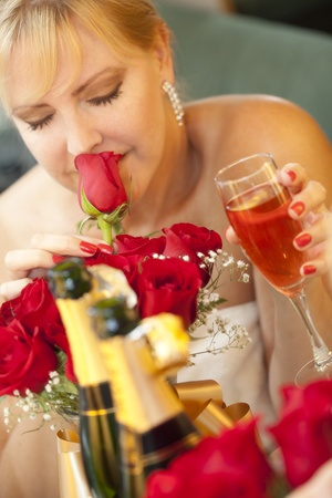 Attractive Blonde Woman Smells Roses at Mirror Near Champagne. photo