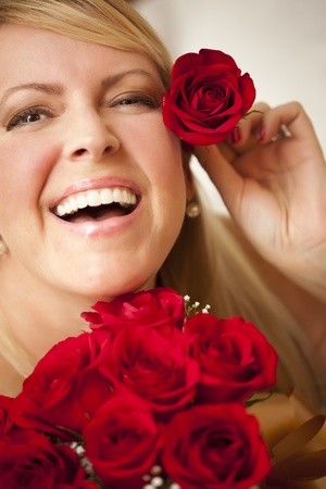 Beautiful Woman with a Bunch of Red Roses and Places One Above Her Ear. photo
