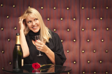 Sensual Smiling Beautiful Blonde Woman Sitting Near Champagne and Rose. Stock Photo
