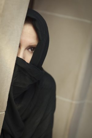 indonesia girl: Cautious Islamic Woman in a Window Pane Wearing Traditional Burqa or Niqab. Stock Photo