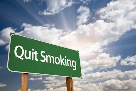 fumando: Dejar de fumar Green Road Sign con nubes dramáticas, rayos del sol y del cielo.