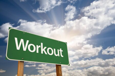get a workout: Workout Green Road Sign with Dramatic Clouds, Sun Rays and Sky. Stock Photo