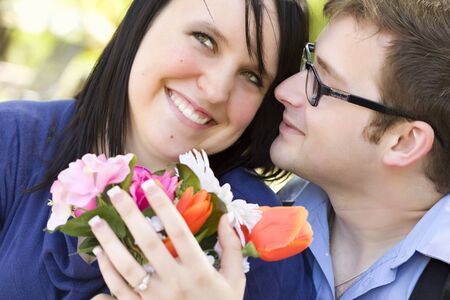 Attractive Young Man Gives Flowers to His Fiance Wearing the Engagement Ring  Stock Photo