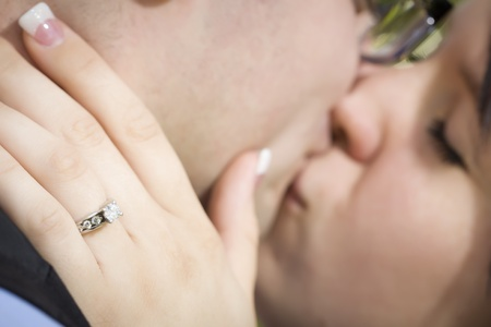 Young Female Hand with Engagement Ring Touching Fiance's Face as They Kiss with Selective Focus on the Ring. Stock Photo - 14023535