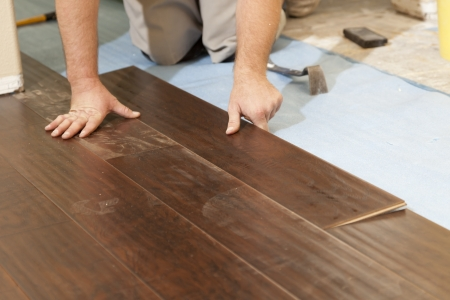 RENOVATE: Man Installing New Laminate Wood Flooring Abstract.