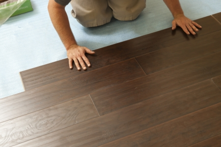 Man Installing New Laminate Wood Flooring Abstract. photo