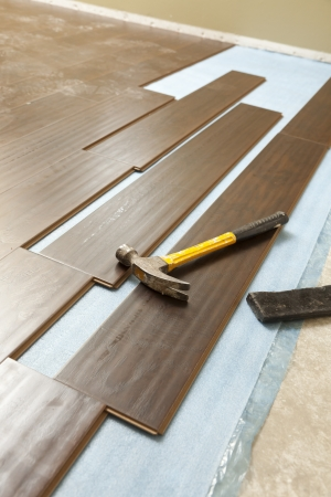 laminate: Hammer and Block with New Laminate Flooring Abstract.