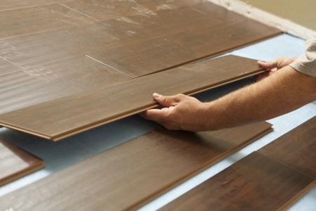 Man Installing New Laminate Wood Flooring Abstract. photo
