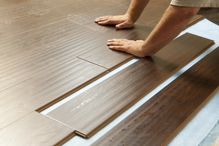 home improvement: Man Installing New Laminate Wood Flooring Abstract.