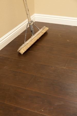 Push Broom On A Newly Installed Laminate Floor And New Baseboards