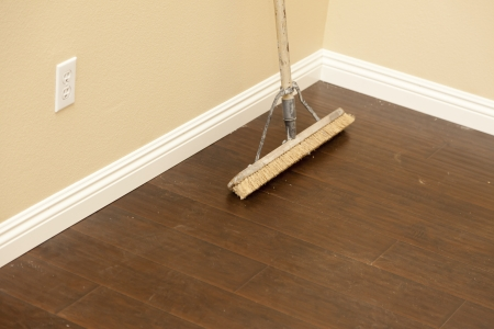 housecleaning: Push Broom on a Newly Installed Laminate Floor and New Baseboards.