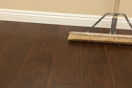 Push Broom on a Newly Installed Laminate Floor and New Baseboards. Stock Photo - 14202954