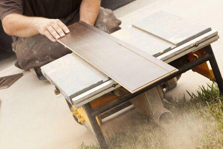 Contractor Using Circular Saw Cutting of New Laminate Flooring Renovation. photo