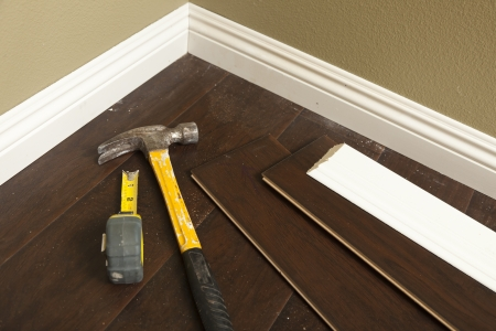 Hammer, Laminate Flooring and New Baseboard Molding Abstract. photo