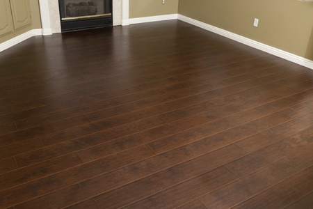 Beautiful Newly Installed Brown Laminate Flooring and Baseboards in Home.