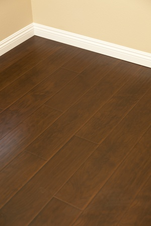 Beautiful Newly Installed Brown Laminate Flooring and Baseboards in Home. photo