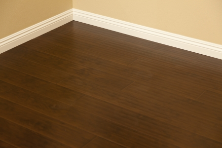 corner house: Beautiful Newly Installed Brown Laminate Flooring and Baseboards in Home.
