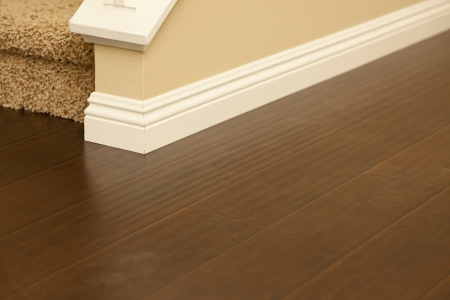 hardwood: Beautiful Newly Installed Brown Laminate Flooring and Baseboards in Home.