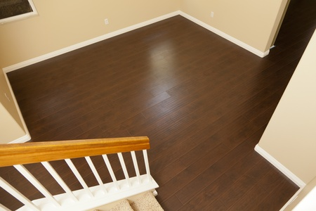 flooring: Beautiful Newly Installed Brown Laminate Flooring and Baseboards in Home.
