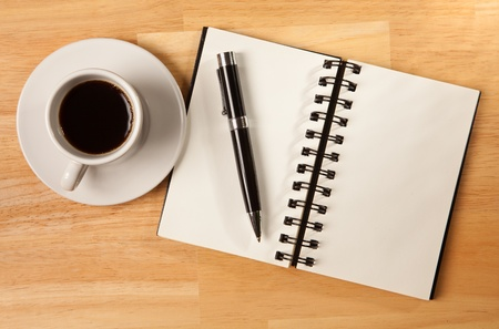 above head: Blank Spiral Note Pad, Cup of Coffee and Pen on Wood Background.