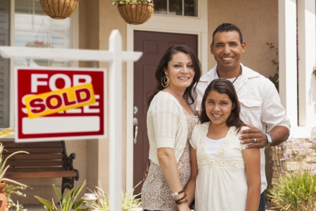 estate: Hispanic Mother, Father and Daughter in Front of Their New Home with Sold Home For Sale Real Estate Sign.
