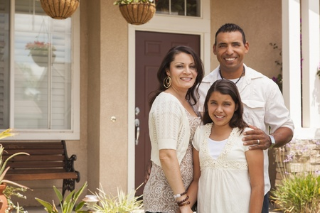 latino family: Hispanic Mother, Father and Daughter in Front of Their Home.
