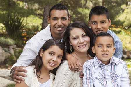 single family home: Happy Attractive Hispanic Family Portrait Outdoors In the Park.