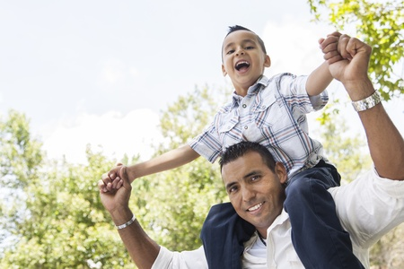 Hispanic Father and Son Having Fun Together Riding on Dads Back in the Park.