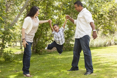 Happy Hispanic Mother and Father Swinging Son in the Park. 免版税图像