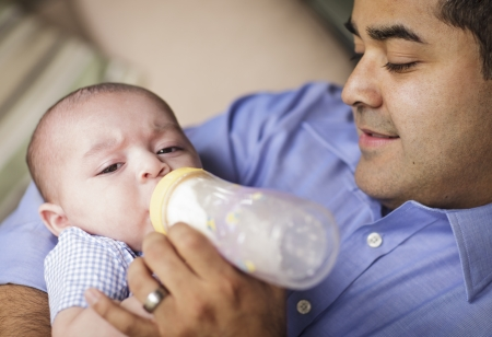single father: Happy Hispanic Father Bottle Feading His Very Content Son.