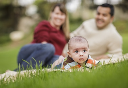 mixed race baby: Happy Mixed Race Baby Boy and Parents Playing Outdoors in the Park. Stock Photo