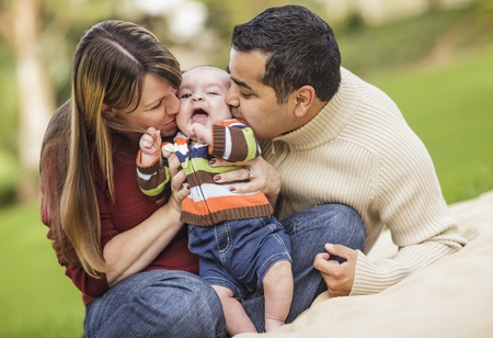 giggling: Happy Mixed Race Parents Playing with Their Giggling Son.