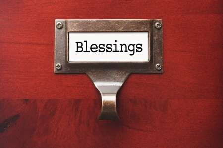 blessings: Lustrous Wooden Cabinet with Blessings File Label in Dramatic LIght. Stock Photo