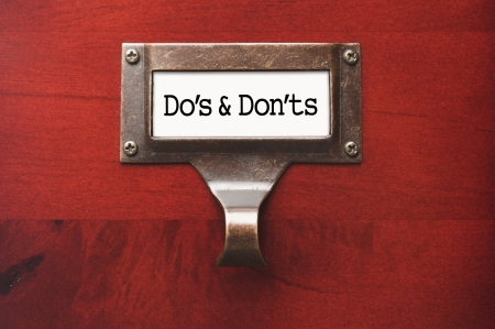 Lustrous Wooden Cabinet with Do's and Don'ts File Label in Dramatic LIght. Imagens