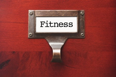 lustrous: Lustrous Wooden Cabinet with Fitness File Label in Dramatic LIght. Stock Photo