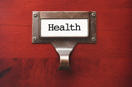 lustrous: Lustrous Wooden Cabinet with Health File Label in Dramatic LIght. Stock Photo