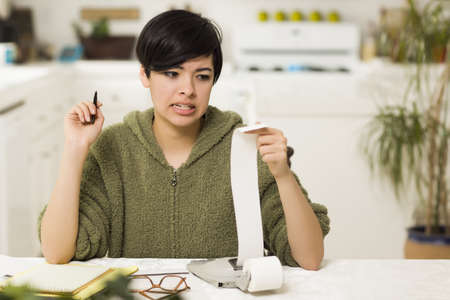 agonizing: Mixed Race Young Female Agonizing Over Financial Calculations in Her Kitchen.